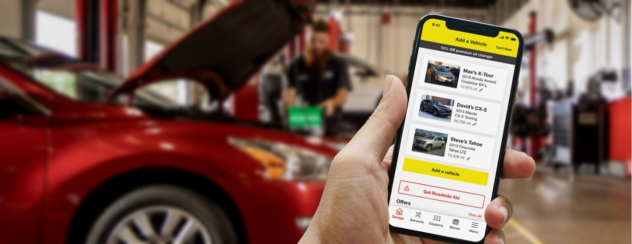 Hand holding mobile device showing Tires Plus mobile app