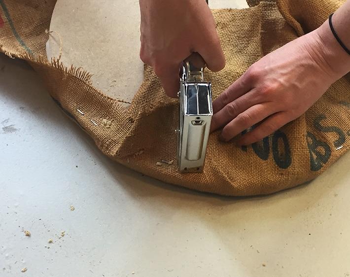 Step 8 - DIY Ottoman - Stapling burlap to plywood