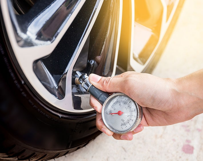 Man checking tire pressure using hand gauge