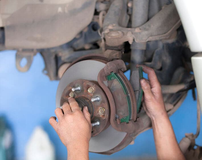 bear hands working on a brake pad