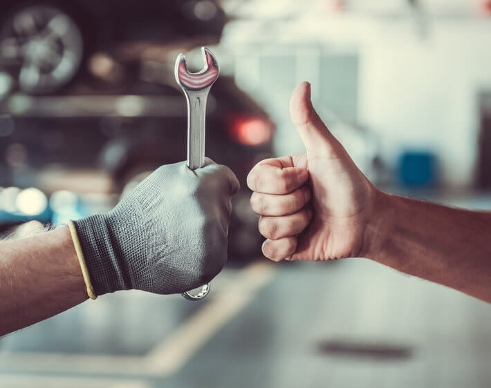 technician holding wrench fist bumping customer