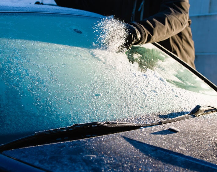 Man wearing gloves scraping windshield frost off his windshield in the morning sun