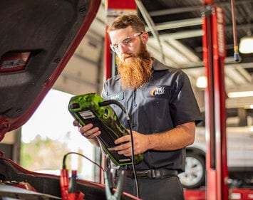 Bearded Tire Plus technician performing free car battery test