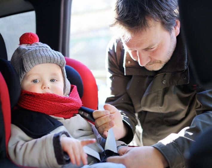 father securing baby in car seat