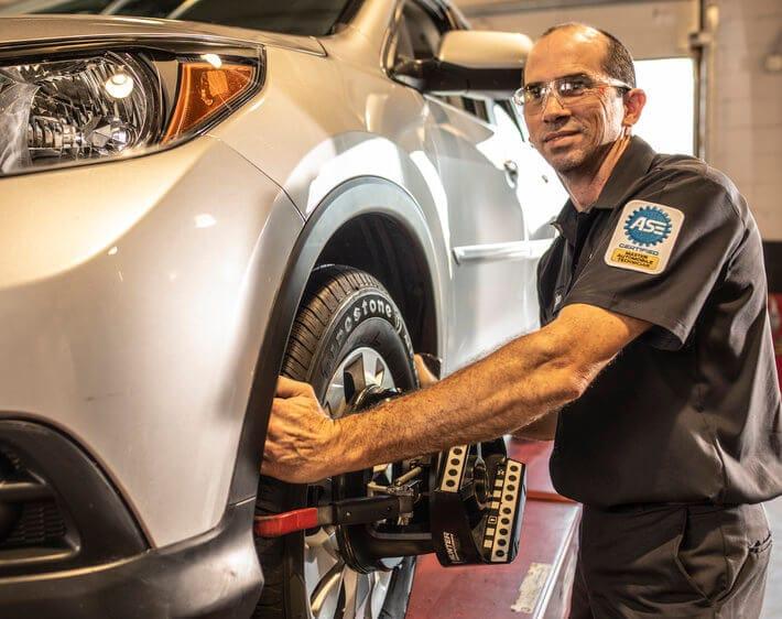 Tires Plus technician doing a wheel alignment