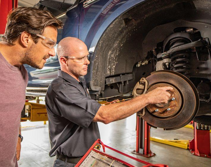 Tires Plus technician explains brake service to male customer wearing protective eye gear