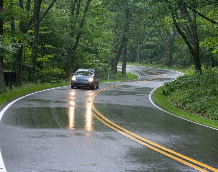 hatchback driving down winding wet road