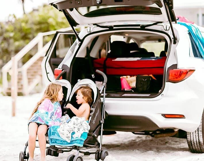 Children in stroller in front of car