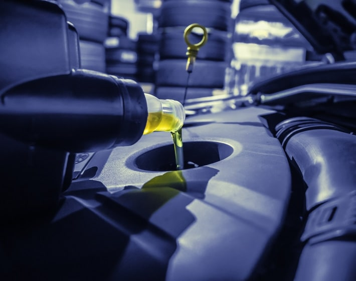Pouring oil into a car engine