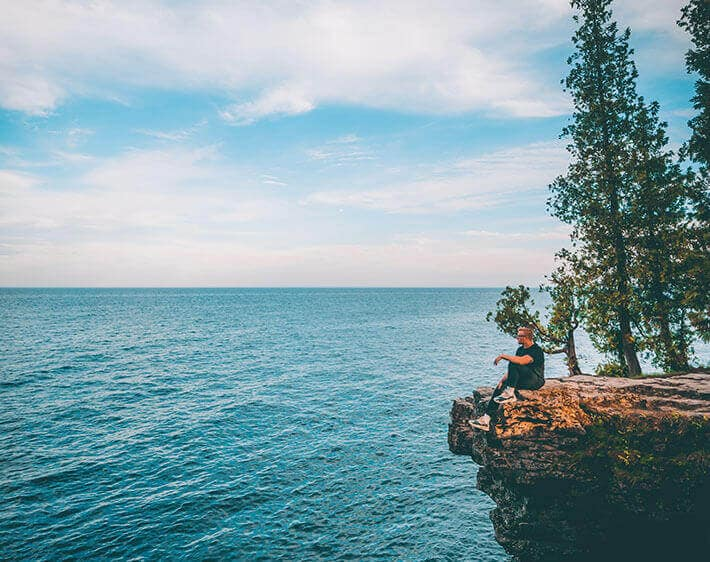 Man overlooking ocean from a cliff