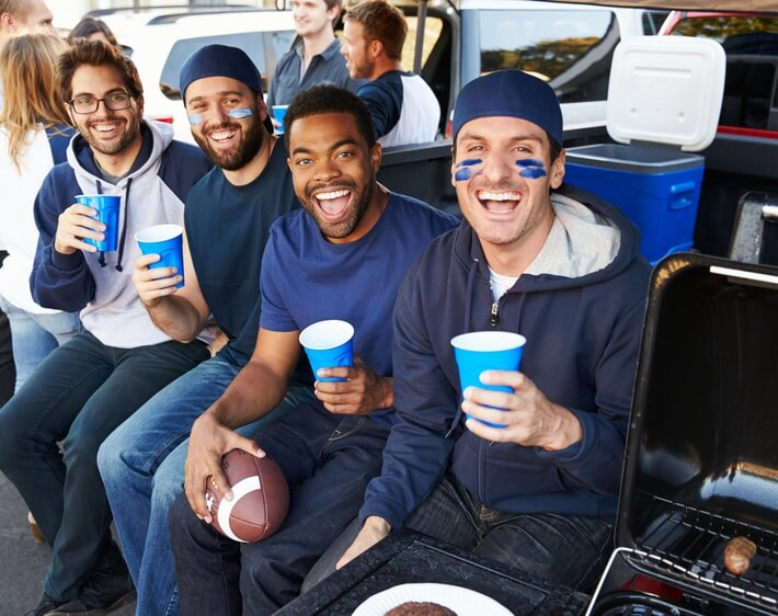 Four friends tailgating in the back of a truck