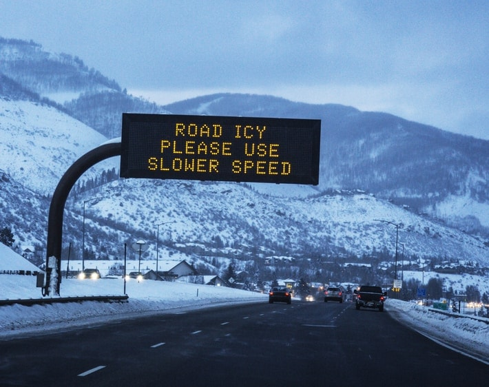 Road icy please use slower speed sign over highway