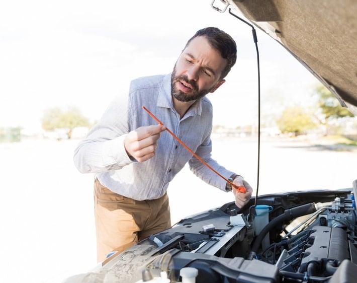 Man checking oil dipstick