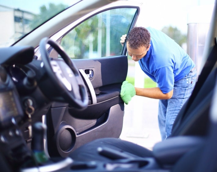 Man wiping down the inside of a car door