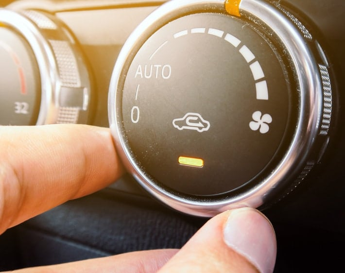 Hand turning the air conditioning knob