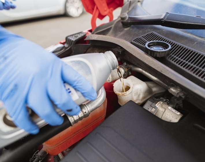 Person pouring brake fluid into car