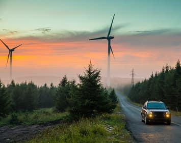 Car driving down foggy road at dawn with wind turbines in the background