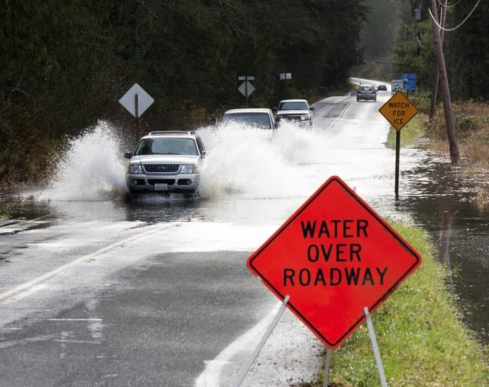 "Line of Cars on Two-Way Road Driving Through Deep Puddle with Bright Orange ""Water Over Roadway"" Sign at Forefront of Image."