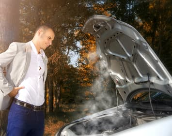 Businessman standing by the car with hood open trying to solve the problem. Smoke coming out of the engine.