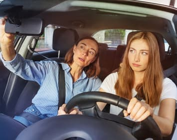 Mother illustrating how to use rear view mirror to teenage daughter in driver's seat.