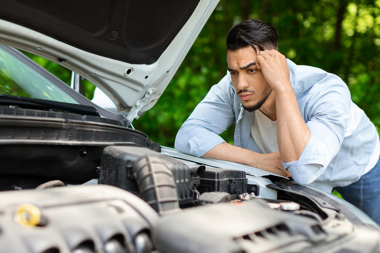image of a confused man looking at his car engine
